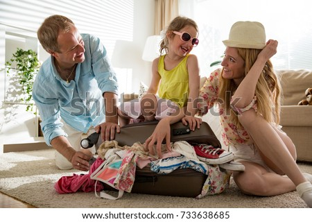 Happy family in colorful summer outfit packing clothes in staffed suitcase. Little girl sitting on baggage bag, ready for travel.