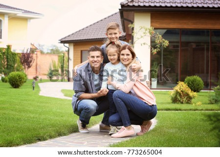 Happy family in courtyard near their house