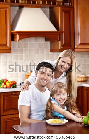 Happy family in kitchen look in camera