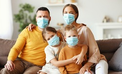 happy family in protective medical masks in the midst of the coronavirus pandemic at home