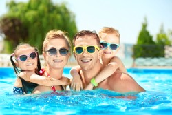Happy family in swimming pool at water park