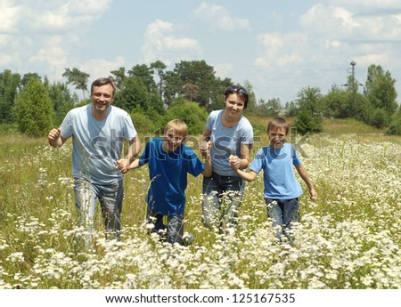 happy family in the blue in a summer park