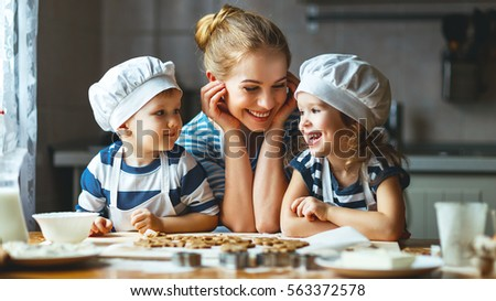 happy family in the kitchen. mother and  children preparing the dough, bake cookies #563372578