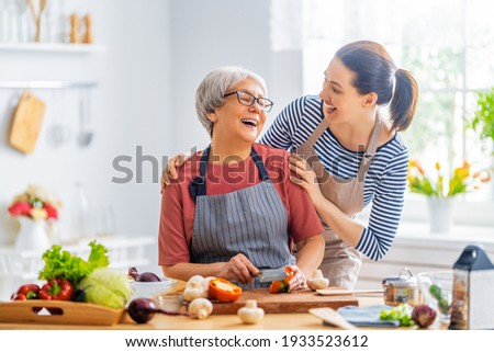 Happy family in the kitchen. Mother and her adult daughter are preparing proper meal.