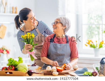 Happy family in the kitchen. Mother and her adult daughter are preparing proper meal. Woman is giving flowers to her mom.