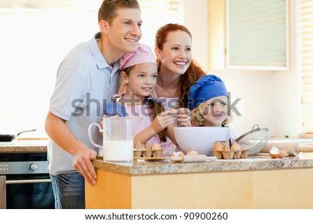 Happy family in the kitchen with baking ingredients