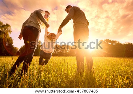 Happy family in the park evening light. The lights of a sun. Mom, dad and baby happy walk at sunset. The concept of a happy family.Parents hold the baby\'s hands.