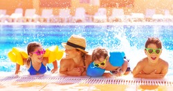 Happy family in the pool, having fun in the water, mother with three kids enjoying aqua park, beach resort, summer holidays, vacation concept