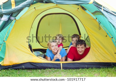 Happy family in the tent. Father, mother and child camping