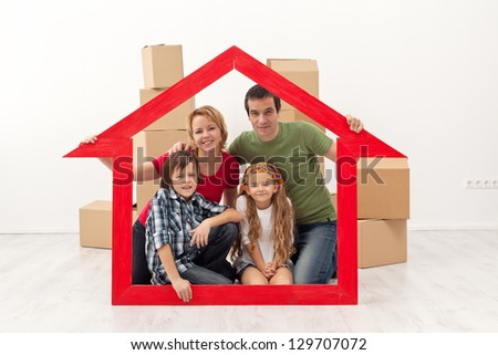 Happy family in their new home - with house shaped frame and cardboard boxes