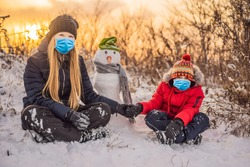 Happy family in warm clothing wearing a medical mask during COVID-19 coronavirus. Smiling mother and son making a snowman outdoor. The concept of winter activities