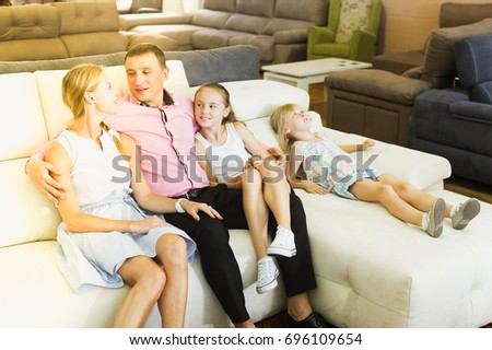 Happy family inspecting new sofa in modern furniture store