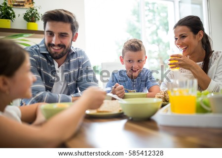Happy family interacting while having breakfast. Social distancing and self isolation in quarantine lockdown for Coronavirus Covid19