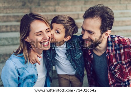 Happy family is having fun outdoors. Father, mother and son are spending time together. #714026542