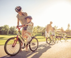 Happy family is riding bikes outdoors and smiling. Parents are teaching their children
