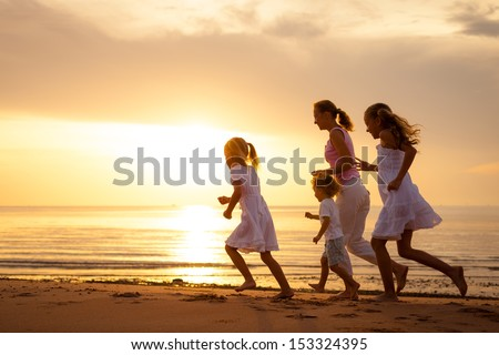 Happy family is running at the beach on the dawn time