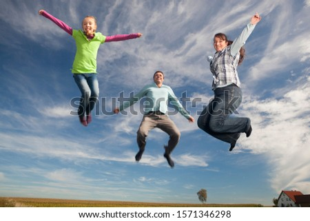 Happy family jumping in mid-air near house