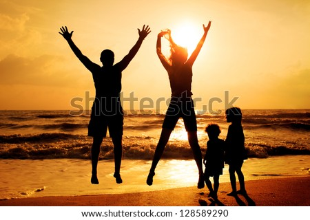 Happy family jumping on the beach on the dawn time