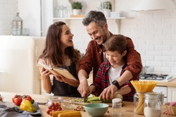 Happy family laughing loud. Mother, father and preschool son cooking on home kitchen. Mom holding cookbook. Dad helping child to chop celery for salad. Funny weekends. Communication and fun