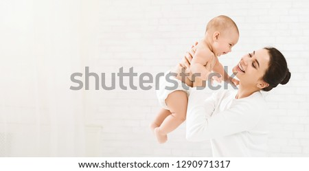 Happy family. Laughing mother lifting her adorable newborn baby son in air, panorama, copy space