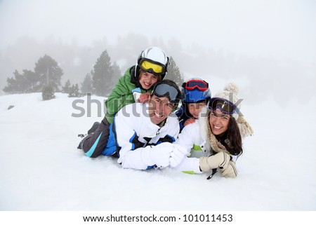 Happy family laying down in the snow