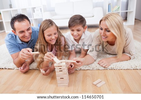 Happy Family Laying On Carpet Playing With The Wooden Blocks At Home