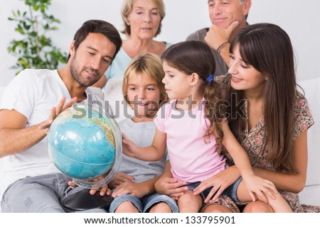 Happy family looking at globe on the couch