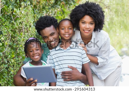 Happy family looking at tablet pc in the garden at home