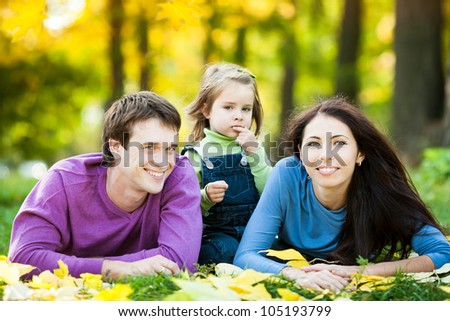 Happy family lying against blurred leaves background in autumn park