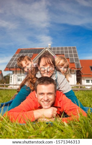 Happy family lying in grass in front of house with solar panels