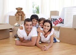 Happy family lying on floor after buying new house