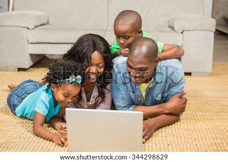 Happy family lying on the floor using laptop in the living room #344298629