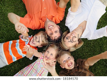 Happy family lying on the grass and holding hands