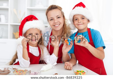 Happy family making and decorating christmas cookies