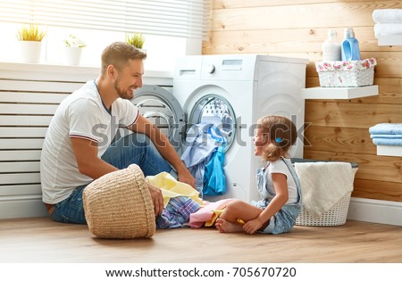 Happy family man father  householder and child daughter in laundry with washing machine  #705670720