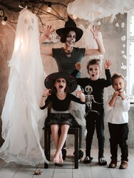 happy family mom and kids in costumes and makeup at the Halloween celebration on the background of the Ghost scenery, carnival party