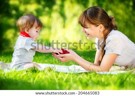 Happy family, mom and little son having fun in the park. Raspberry in his hands. Summer vacations concept.