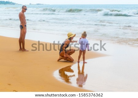 happy family, mom dad and little daughter on the shore of the sandy beach by ocean spend time and walk.