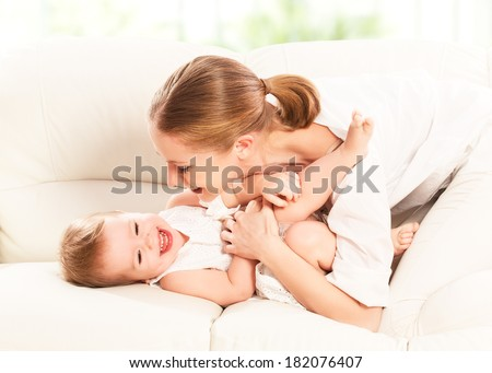 happy family. Mother and baby daughter plays at home on the sofa