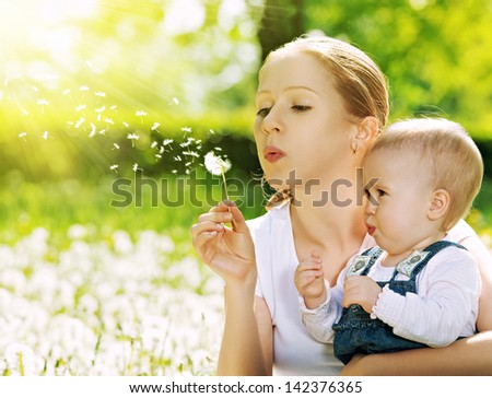 happy family. Mother and baby girl blowing on a dandelion flower on the nature in the summer in the park