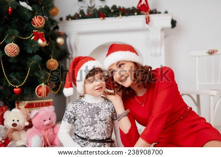 Happy family mother and baby in red Christmas hats. Happy family mother and baby little daughter playing in the winter for the Christmas holidays.