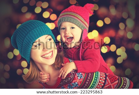 Stock Photo happy family mother and baby little daughter playing in the winter for the Christmas holidays