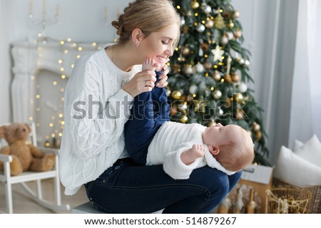happy family mother and baby little son playing home on Christmas holidays. New Year\'s holidays. Toddler with mom in the festively decorated room with Christmas tree. Portrait of mother and baby boy