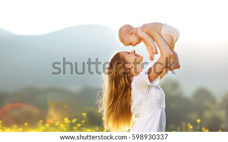 Happy family mother and baby son in a meadow  yellow flowers on nature in summer