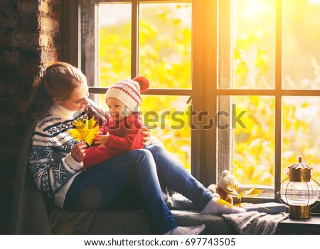happy family mother and baby son in autumn window