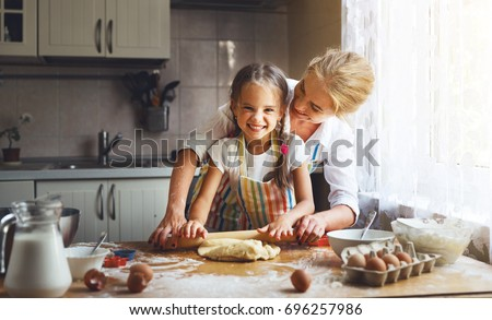Happy family mother and child daughter bake kneading dough in the kitchen #696257986