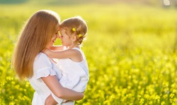 Happy family mother and child daughter embrace on yellow flowers on nature in summer
