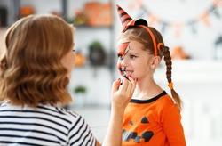 happy family mother and child daughter getting ready for halloween make make-up