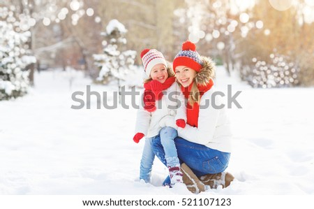 happy family mother and child daughter having fun, playing at winter walk outdoors