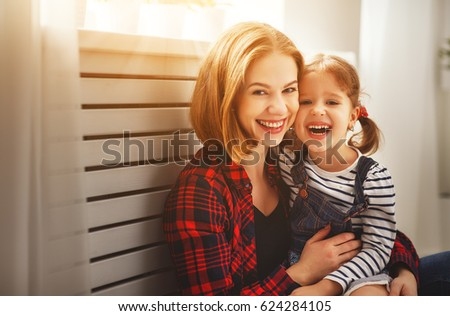 Happy family mother and child daughter laugh play and cuddle
